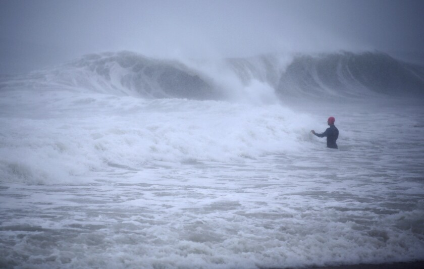 A man walks in the ocean.