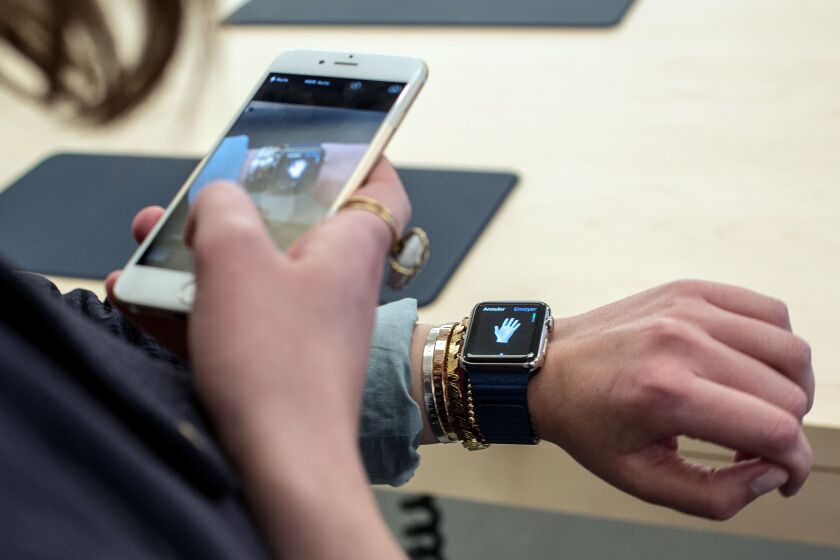 A customer uses an iPhone 6 smartphone to take a photo of a model of the Apple Watch.