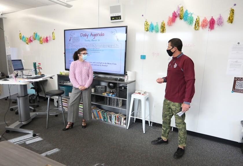 Principal Jason Allemann, right, checks in with teacher Dawn Hunnicutt at Laguna Beach High on March 17.