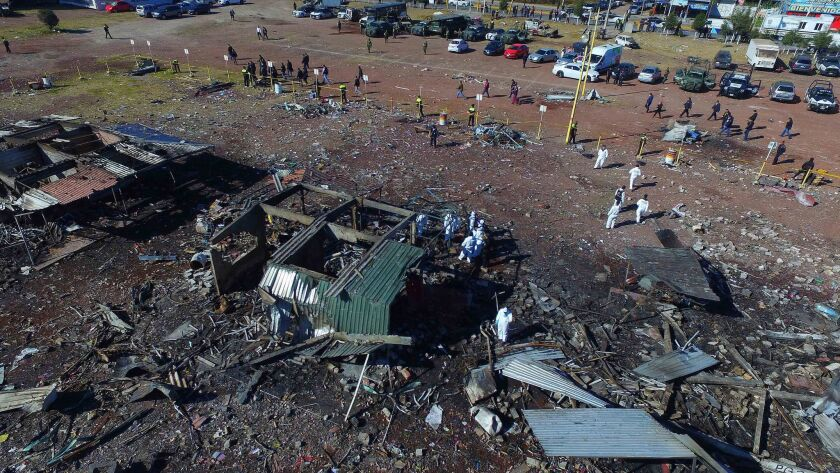 Investigators walk through the scorched rubble of the open-air San Pablito fireworks market on Dec. 21, 2016. The market in Tultepec, on the outskirts of Mexico City, exploded the day before.