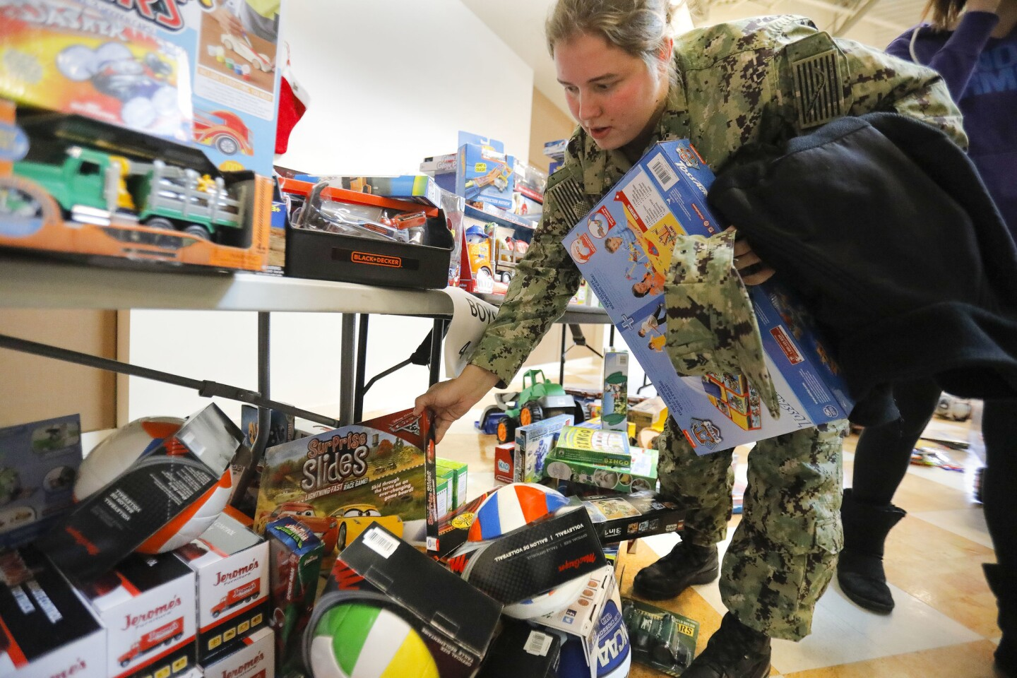 Navy Petty Officer 2nd Class Savanna Nowell picks out gifts for her children while visiting the 27th annual Military Family Holiday Toy Program at the Armed Services YMCA San Diego Chapel in Murphy Canyon.