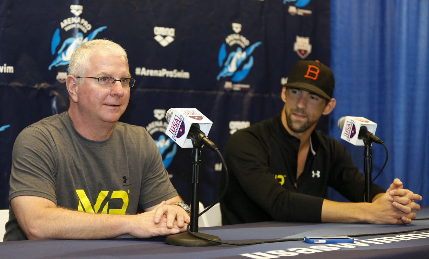 Bob Bowman, left, answers a question as Michael Phelps looks on at a news conference at the Arena Pro Swim Series swim meet in Charlotte, N.C.