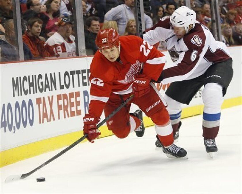 Detroit Red Wings right wing Jordin Tootoo (22) tries to maintain control of the puck against Colorado Avalanche defenseman Erik Johnson (6) in the second period of an NHL hockey game Monday, April 1, 2013, in Detroit. (AP Photo/Duane Burleson)
