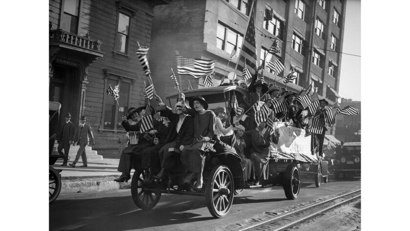 Nov. 11, 1918: Workers from Boos Brothers cafeterias ride through Los Angeles waving flags and singing war songs after Germany's surrender ended World War I.