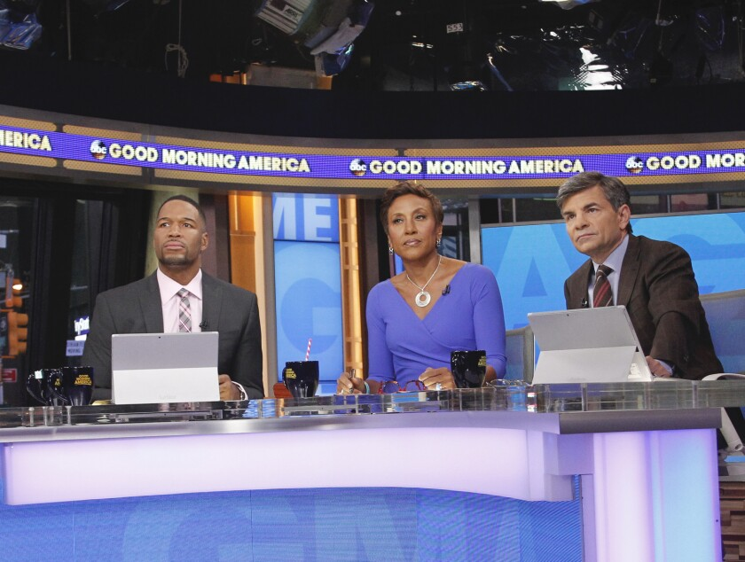 """Michael Strahan, Robin Roberts and George Stephanopoulos seated on the set of ABC's """"Good Morning America."""""""