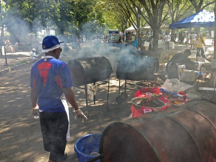 Food vendors prepare jerk chicken in drum cookers along Eastern Parkway before the start of the annual West Indian Day Parade in the Brooklyn borough of New York Monday, Sept 1, 2014. Hours before the parade, police reported multiple shootings overnight, one of them deadly, near the route for the political see-and-be-seen event, which celebrates Caribbean culture and echoes traditional pre-Lenten Carnival festivities. (AP Photo/Mark Lennihan)