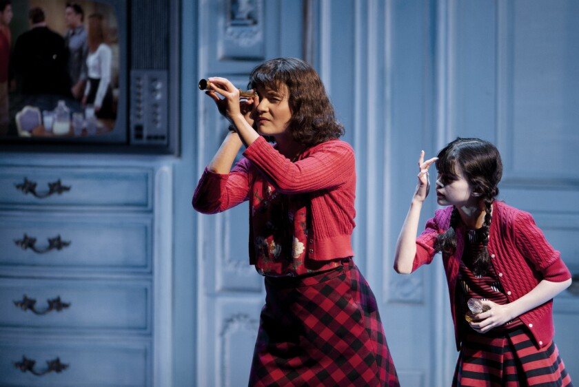"""Amélie (Phillipa Soo), observed by her younger self (Savvy Crawford), makes a discovery in """"Amélie, A New Musical"""" at the Ahmanson Theatre."""