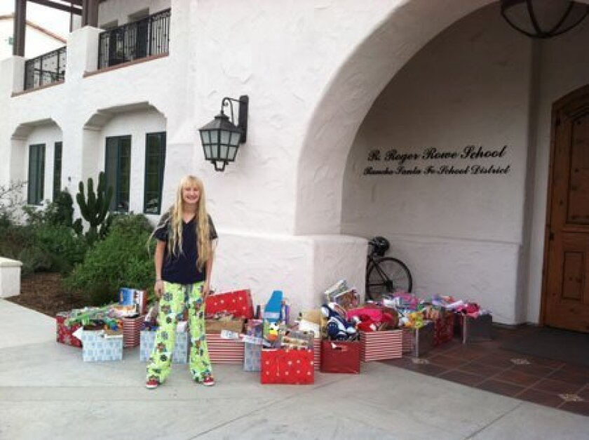 Sarah Lackey, Monarch School Drive coordinator, with donations from R. Roger Rowe School.