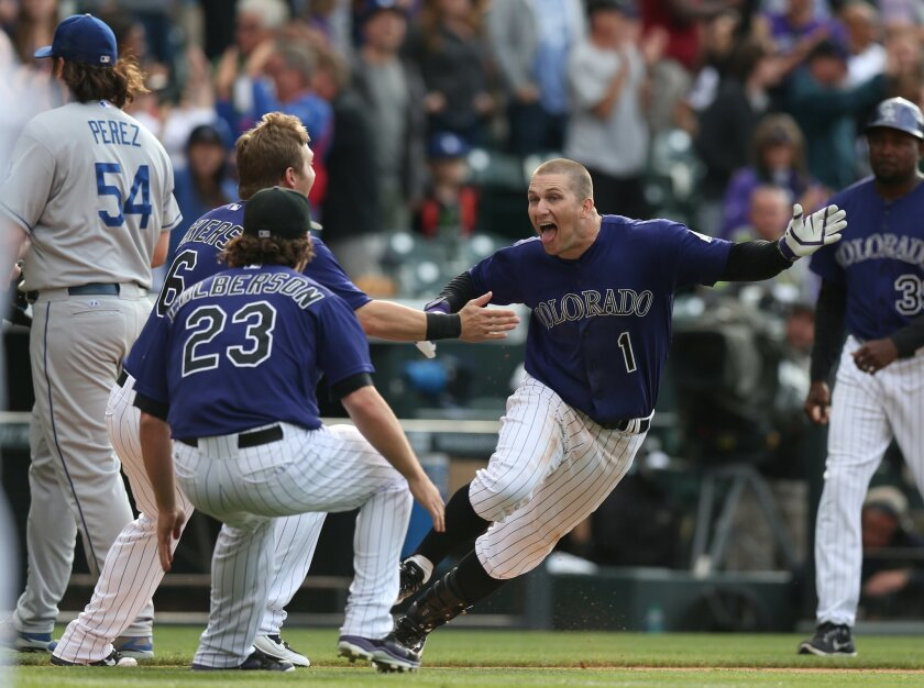 As Los Angeles Dodgers relief pitcher Chris Perez, far left, heads to the dugout, Colorado Rockies' Brandon Barnes, front right, celebrates driving in the winning run with teammates Corey Dickerson and Charlie Culberson, front left, in the 10th inning of the Rockies' 5-4 victory in 10 innings in a baseball game in Denver on Saturday, June 7, 2014. (AP Photo/David Zalubowski)