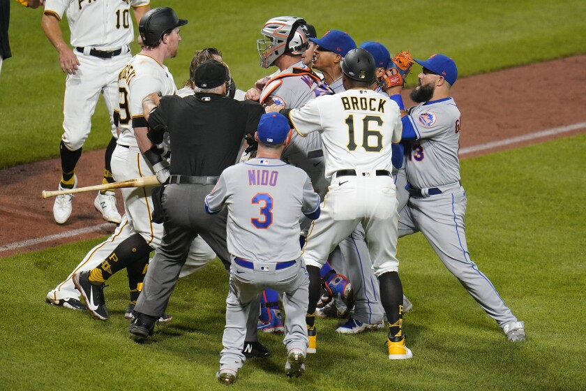 Pittsburgh Pirates' John Nogowski, left, and New York Mets starting pitcher Marcus Stroman, fourth from right, exchange words as players and coaches arrive during the sixth inning of a baseball game Friday, July 16, 2021 in Pittsburgh. (AP Photo/Gene J. Puskar)
