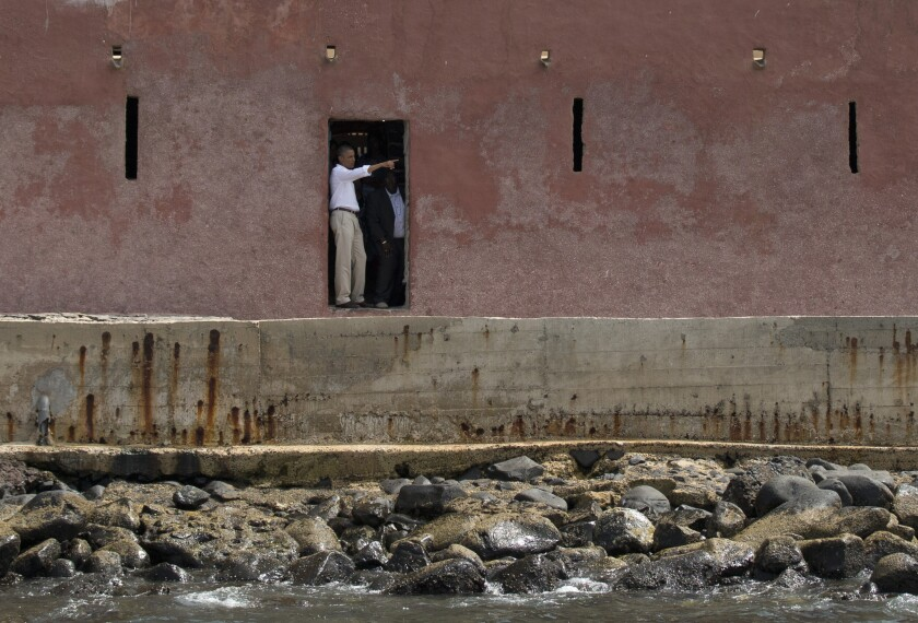 """President Obama, left, talks with Slave House curator Eloi Coly as they look out to sea through the """"Door of No Return"""" on Goree Island, in Dakar, Senegal on Thursday."""