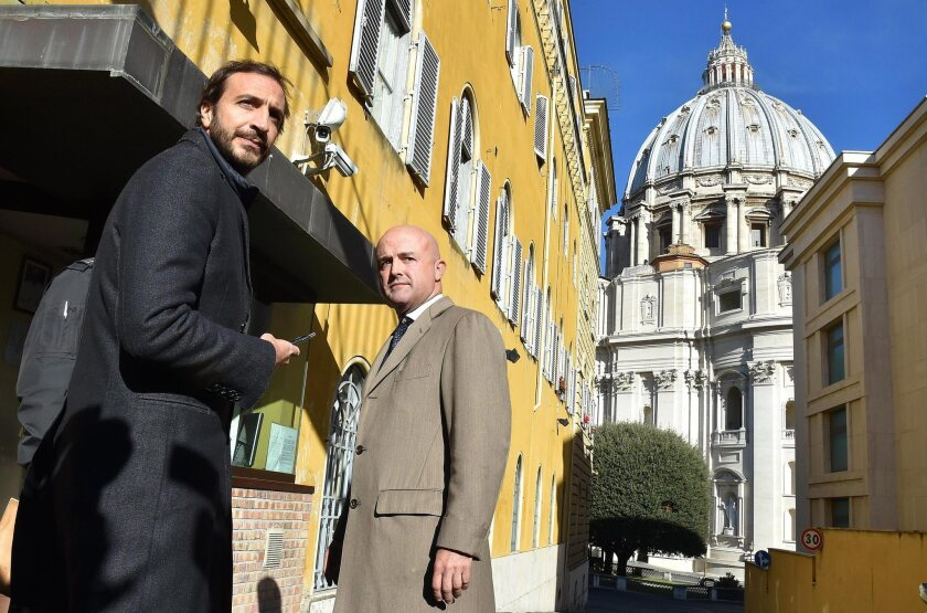 Italian journalists-writers Gianluigi Nuzzi, right, and Emiliano Fittipaldi arrive for the first day of their trial at the Vatican on Tuesday. The Vatican has placed the two Italian journalists under investigation in its probe over leaked documents that revealed waste, greed and mismanagement at the highest levels of the Roman Catholic Church.