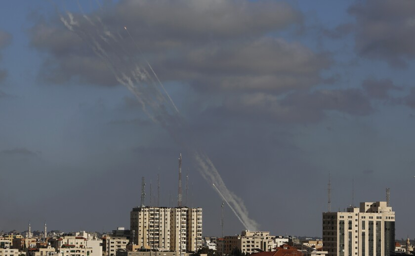Rockets streak into the sky above a line of buildings.