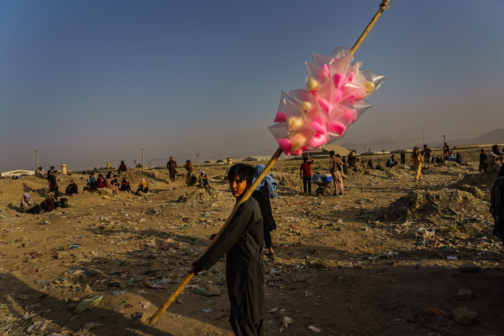 A boy holds a pole with cotton candy in an area with people standing and sitting on the ground.