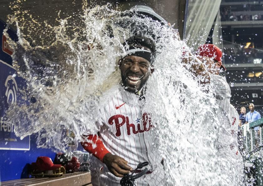 Andrew McCutchen, de los Filis de Filadelfia, es bañado con agua por su compañero Archie Bradley después de que conectara un jonrón de tres carreras en la parte baja de la novena entrada del partido contra los Nacionales de Washington, en Filadelfia, el lunes 26 de julio de 2021. (AP Foto/Laurence Kesterson)