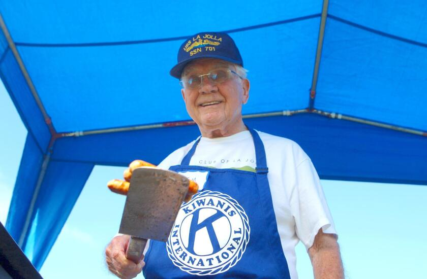 Tom Henry, nicknamed 'The Sausage King' by Kiwanis members for his mastery on the grill, surveys his sausage kingdom.