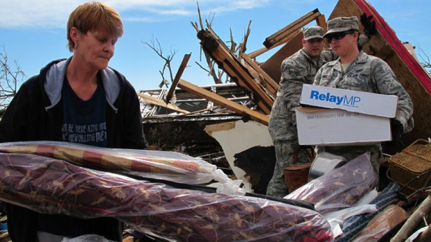 Josephine Owings, 62, who survived a direct hit by a tornado on her rented home in Moore, Okla., Monday afternoon, gets help recovering belongings Tuesday. Owings returned to salvage items from her home-based seamstress business.