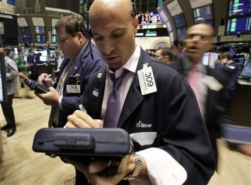 In this Oct. 6, 2010 photograph, traders John Santiago, left, and Steven Marcus, center, work on the floor of the New York Stock Exchange. Stock futures were little changed Thursday, Oct. 7, as traders avoided any big moves before a key reading on unemployment claims and the start of earnings season.(AP Photo/Richard Drew)