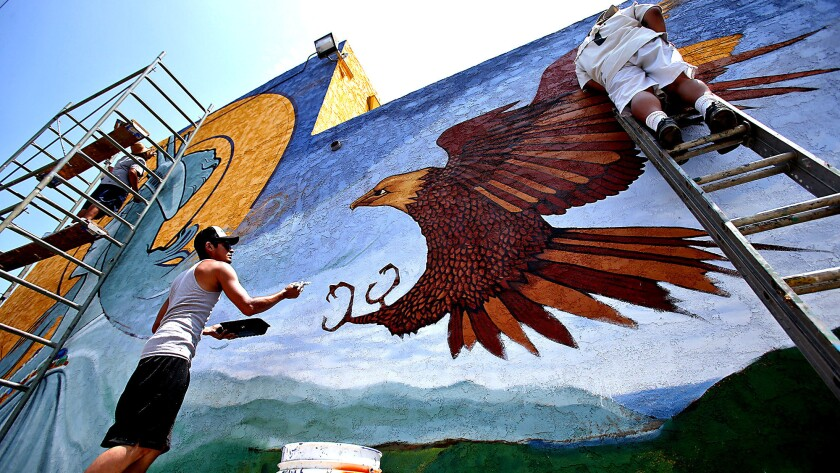 Levi Ponce, center, is assisted by fellow artists as he works on a painting on Mural Mile on Van Nuys Boulevard.