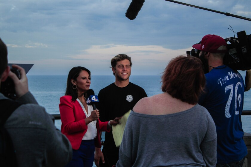 Santa Barbara's Conner Coffin, currently the No. 12-ranked surfer in the world, speaks with a reporter from KNBC Los Angeles during a live broadcast Tuesday morning on the Huntington Beach Pier.