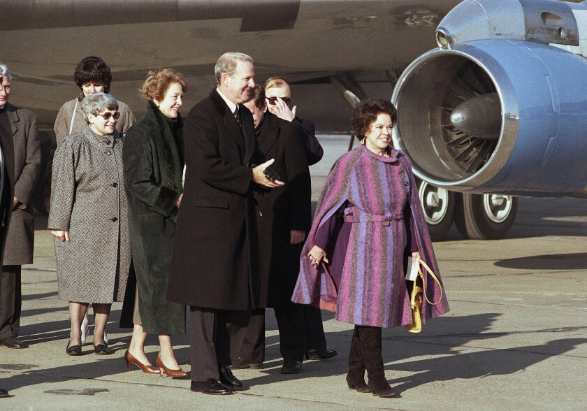 In this Feb. 6, 1990 file photo, U.S. Ambassador to Czechoslovakia Shirley Temple Black, right, leads U.S. Secretary of State James Baker and wife Susan from the plane at Prague Airport.