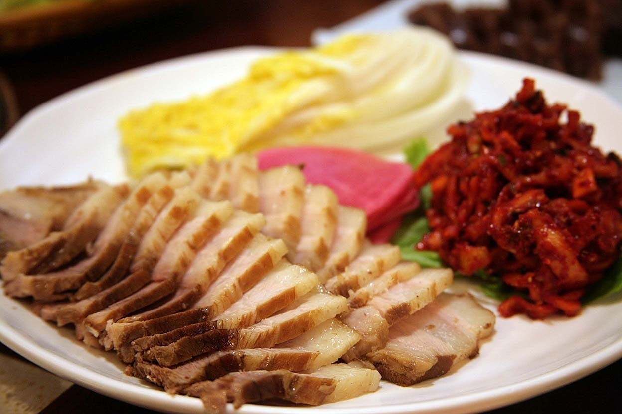 Tender slices of pork come with napa cabbage leaves, jutgal (kimchi filling) and pickled radishes. It's like a deconstructed kimchi dish with pork.