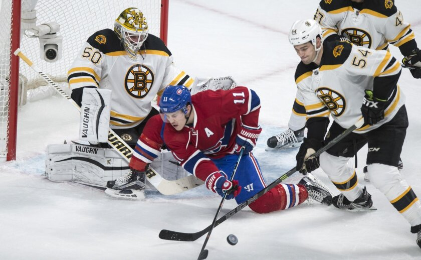 Boston Bruins' defender Adam McQuaid (54) sends the puck away from Montreal Canadiens' Brendan Gallagher (11) in front of goalie Jonas Gustavsson (50) during first period NHL hockey action, in Montreal, on Saturday, Nov. 7, 2015. (Paul Chiasson/The Canadian Press via AP)