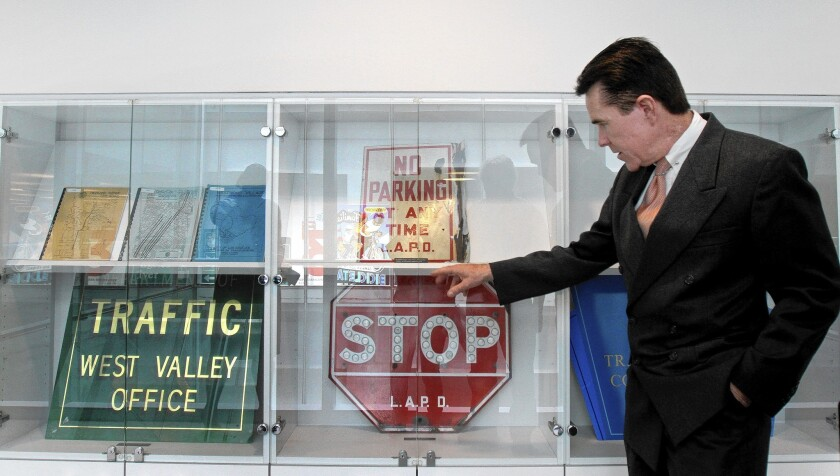 John Fisher, who retired two years ago after 39 years as a city Department of Transportation engineer and assistant general manager, shows vintage street signs at the Caltrans building in downtown Los Angeles. He amassed a collection of the designs and donated them for display.