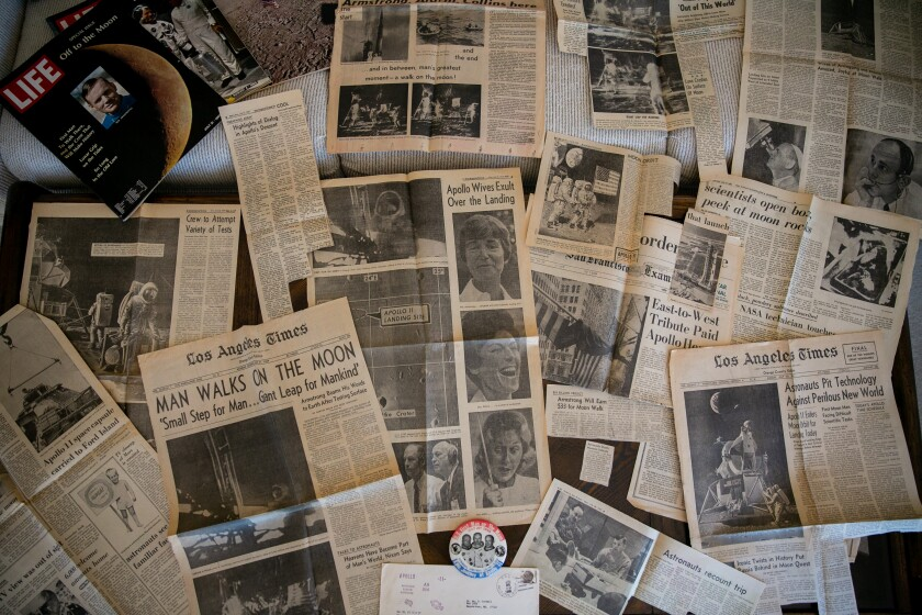 Jeryl Cordell, who witnessed the Apollo 11 capsule splash down on earth from aboard the USS Arlington, displays newspaper clippings from the event in his home on July 19, 2019.