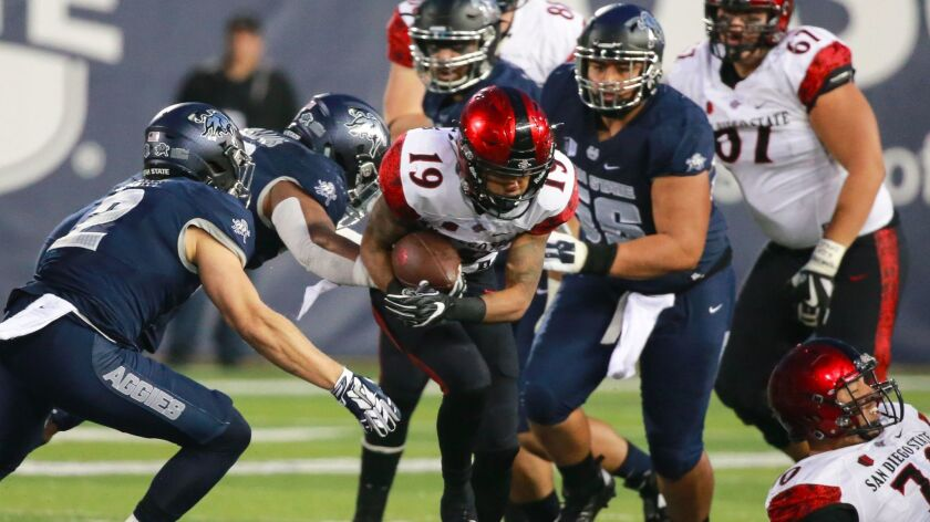 San Diego State running back D.J. Pumphrey runs between Utah State defensive back Dallin Leavitt (2) and nose tackle Gasetoto Schuster (56) during the first quarter at Maverik Stadium.