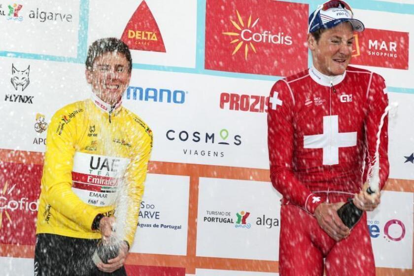 El ciclista eslovaco Tadej Pogacar (i), del equipo UAE Team, celebra el maillot amarillo de líder junto al suizo del Groupama-FDJ Stefan Küng (d), ganador de la contrarreloj de la Volta al Algarve en Lagoa (Portugal), este viernes. El ciclista suizo del Groupama-FDJ Stefan Küng se adjudicó hoy la contrarreloj de la Volta al Algarve lusa, mientras que el joven esloveno Tadej Pogacar logró mantener el maillot amarillo de la General. EFE