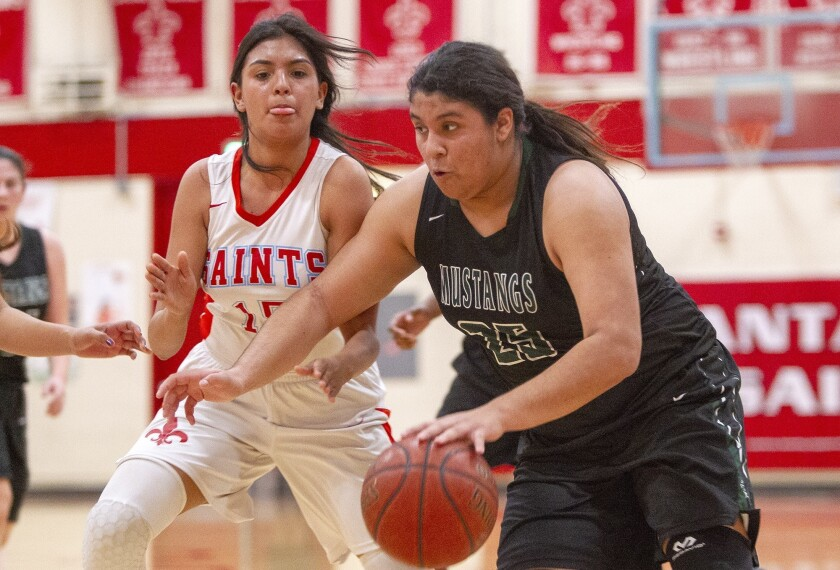 Costa Mesa's Katie Belmontes drives the lane under pressure from Sanat Ana's Valeria Rueda during an