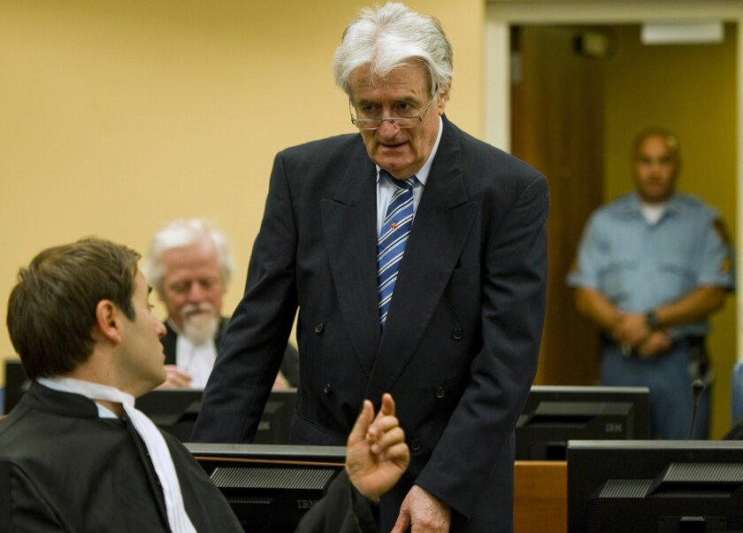 FILE - In this file photo dated Tuesday, Oct. 16, 2012,  former Bosnian Serb leader Radovan Karadzic, stands as he talks to a member of his legal team at the U.N. war crimes tribunal in The Hague, Netherlands. The Yugoslav war crimes tribunal released information Thursday Feb. 18, 2016, that it wil