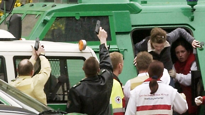 A girl is helped by rescue workers out of a police armored vehicle as officers aim their guns during a school shooting in Erfurt, Germany, in 2002.