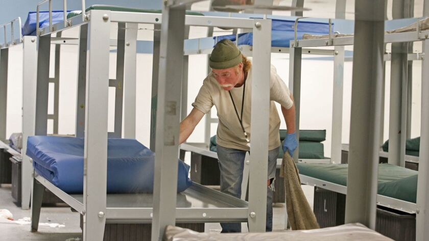 A worker cleans beds in the men's section of the Road Home shelter in Salt Lake City. The shelter serves as many as 1,100 homeless people on busy nights.