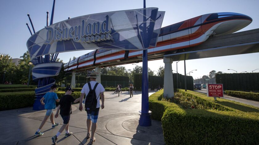 The Disneyland Monorail passes by as people walk under the Disneyland sign in Anaheim. A campaign for a living wage measure in Anaheim has drawn huge donations from unions and the Walt Disney Co. The two sides dispute whether the measure applies to the resort.