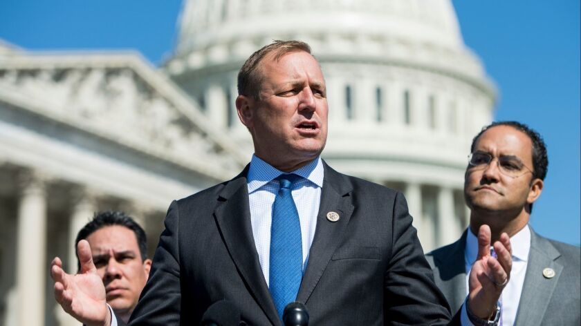Rep. Jeff Denham (R-Turlock), flanked by Rep. Pete Aguilar (D-Redlands), left, and Rep. Will Hurd (R-Texas), speaks on immigration legislation outside the Capitol on April 18, 2018.