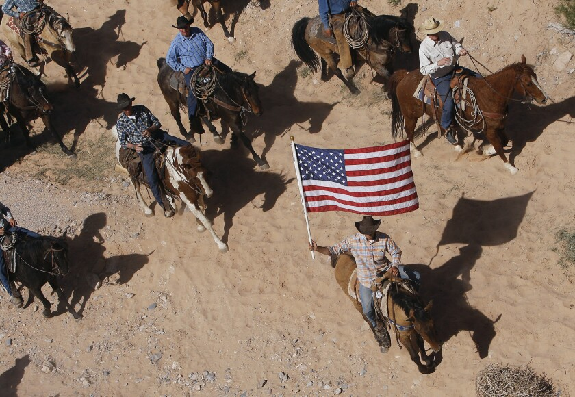 The Bundy family and their supporters fly the American flag as their cattle is released by the Bureau of Land Management back onto public land outside of Bunkerville, Nev., in May. Six defendants stand accused of stopping U.S. agents at gunpoint from rounding up cattle near Bundy's ranch in April 2014.