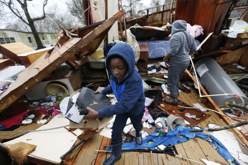 Emma Carter's grandsons comb the remains of her mobile home in Pickens, Miss., after severe weather hit the area on Thursday.