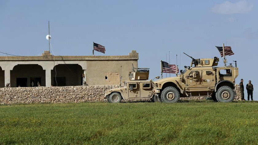 U.S. soldiers wait at a house that was turned into an outpost on a road leading to the front line between Syrian Manbij Military Council fighters and Turkish-backed fighters in Syria on Thursday.