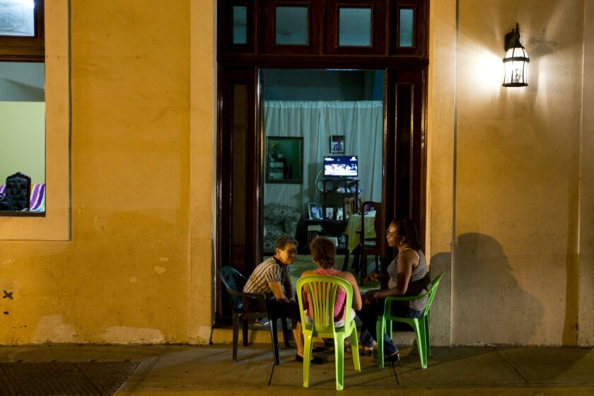 Women talk while sitting out on the sidewalk, as they watch a broadcast of the VII Summit of the Americas near Plaza Bolivar in Panama City, Thursday, April 9, 2015. Panama will host the Summit of the Americas on April 10-11. (AP Photo/Moises Castillo)