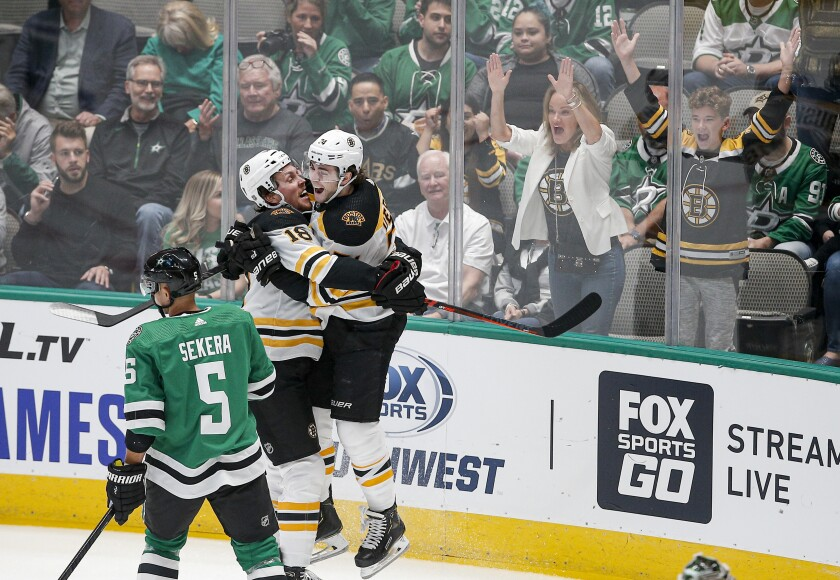Dallas Stars defenseman Andrej Sekera (5) skates past as Boston Bruins forward Brett Ritchie (18) is congratulated by forward Jake DeBrusk (74) after scoring a goal during the first period an NHL hockey game Thursday, Oct. 3, 2019, in Dallas. (AP Photo/Brandon Wade)