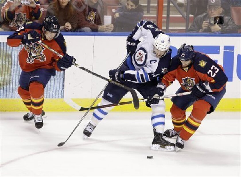 Florida Panthers right wing Scottie Upshall (19) and defenseman Tyson Strachan (23), both of Canada, battle for the puck with Winnipeg Jets left wing Andrew Ladd (16), also of Canada, during the first period of an NHL hockey game, Thursday, Jan. 31, 2013, in Sunrise, Fla. (AP Photo/Wilfredo Lee)