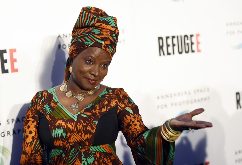 "FILE - In this Thursday, April 21, 2016, file photo, singer and UNICEF Goodwill Ambassador Angelique Kidjo poses at the opening of the new photography exhibit ""REFUGEE"" at The Annenberg Space for Photography in Los Angeles. Kidjo uses her artistry and her activism to connect beyond language and skin color. Kidjo and other international musicians are performing social justice anthems for an online fundraising concert called Peace Through Music: A Global Event for Social Justice. (Photo by Chris Pizzello/Invision/AP, File)"