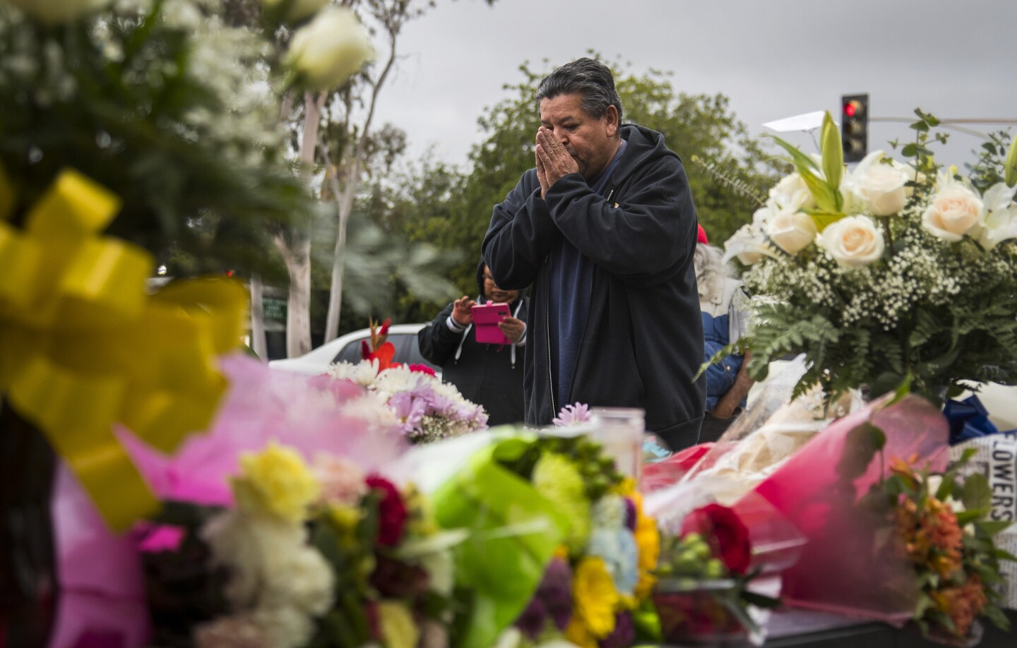 Peter Garcia of Pomona prays at a memorial in front of the Pomona Police Department for fallen Pomona Police Officer Gregory Casillas.