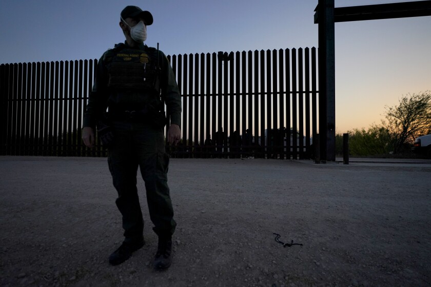 A U.S. Customs and Border Protection agent looks on near a gate on the U.S.-Mexico border wall in Abram-Perezville, Texas
