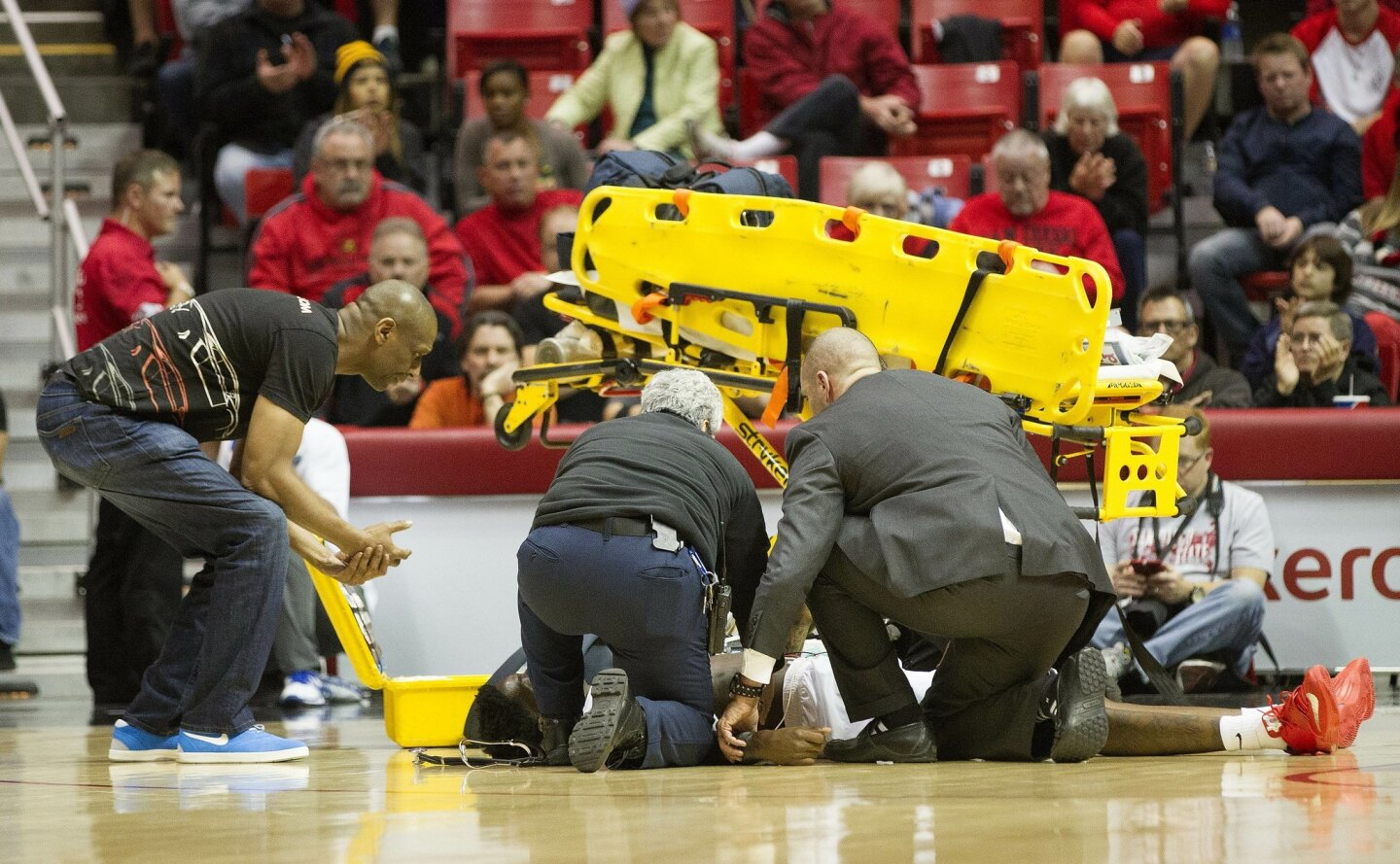 San Diego State Aztecs forward Dwayne Polee II (5) collapses and hits the floor during first half action against UC Riverside. He is seen being attended to by health staff as his father Dwayne Sr. stands over him (left).