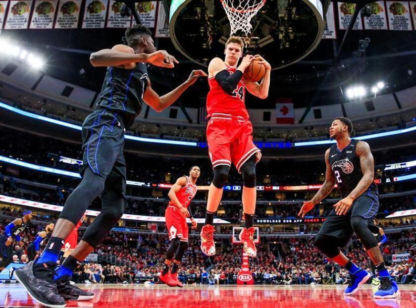 Lauri Markkanen (c), atacante finlandés de los Bulls de Chicago, fue registrado este viernes al ganarle un rebote a Mo Bamba (i) y a Jarell Martin (d), de los Magic de Orlando, durante un partido de la NBA, en el United Center de Chicago (Illinois, EE.UU.). EFE