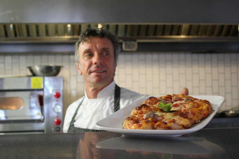 Piazza 1909 co-owner Stafano Ceresoli serves up a pizza with mozzarella, tomato sauce, sausage and bell peppers.