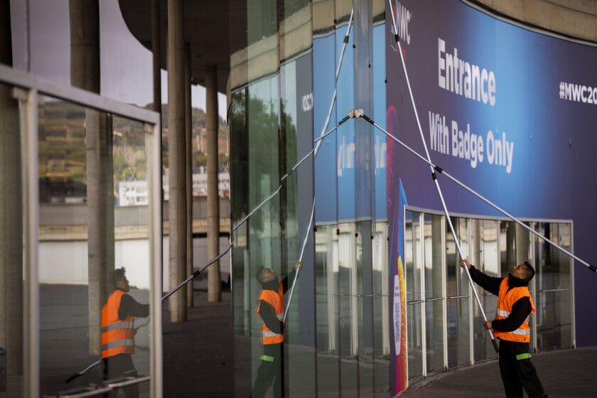 Workers clean the windows in one of the entrances at the Mobile World Congress 2020 venue in Barcelona, Spain, Tuesday, Feb. 11, 2020. Intel Mobile is the latest company announcing that is pulling out of the Mobile World Congress scheduled to be held in Barcelona in late February. Authorities still seem to be committed to hold it, meeting foreign diplomats on Tuesday to brief on the efforts to prevent any spread of the new coronavirus virus during the industry show. (AP Photo/Emilio Morenatti)